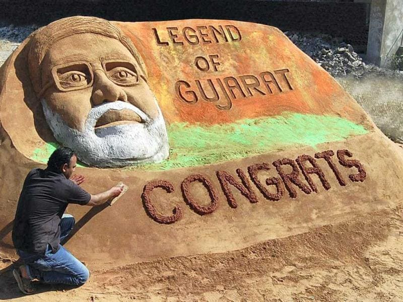 Sand artist Rajesh Muliya creates a sand sculpture of Gujarat chief minister Narendra Modi to mark BJP's victory in Assembly polls in Thangadh. (PTI Photo)