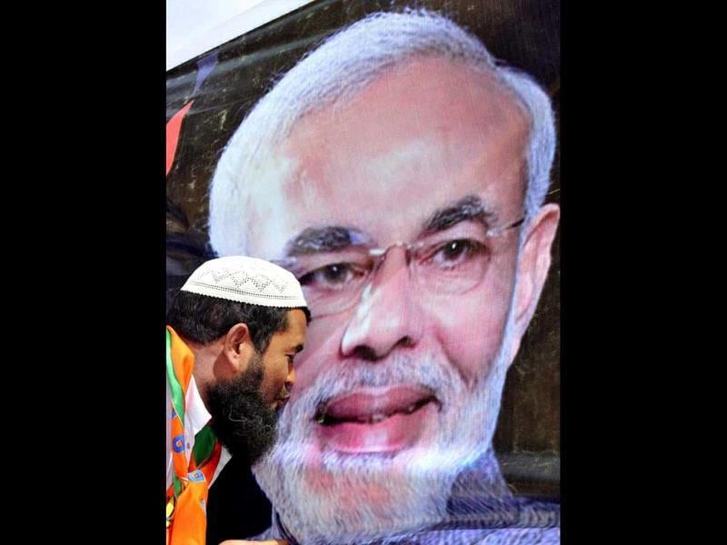 File photo of a Muslim supporter kisses a poster of Narendra Modi to greet him on his success in the Gujarat assembly polls. (PTI Photo)