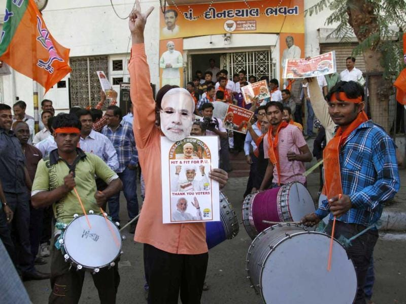 BJP supporter wears a mask of Gujarat chief minister Narendra Modi as he celebrats to early reports stating their party is leading in the Gujarat Assembly elections in Ahmedabad. Supporters of the right-wing Bharatiya Janata Party (BJP) set off firecrackers and waved flags in delight as Modi performed the hat-trick in the state. (AP Photo)
