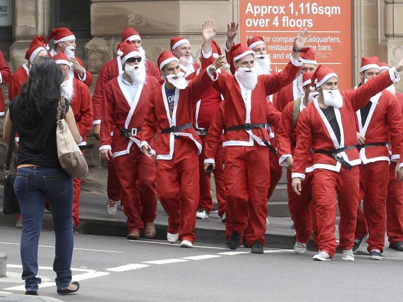 A group of office workers dressed as Santa Claus wave as they walk on a street at the Sydney central business district. AP/Rob Griffith