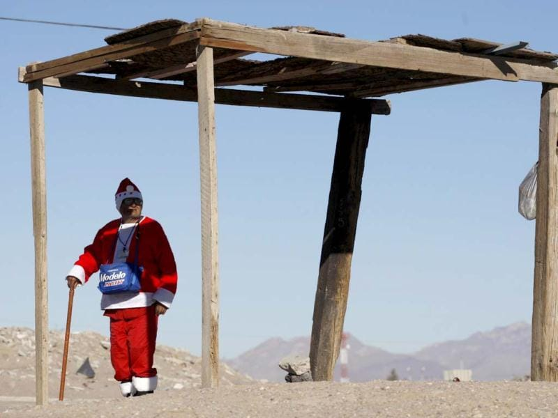 Antonio Martinez, 78, stands in the shade dressed in an old Santa Claus costume while waiting for buses on the outskirts of Ciudad Juarez. Martinez boards the buses and asks for money in return for some candy. Martinez is trying to get enough money so he can buy a toy truck for his grandson for Christmas, according to a local newspaper. Reuters/Jose Luis Gonzalez