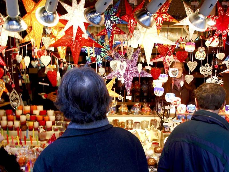 People visit a shop selling illuminated window stars in different colours at Munich's Christmas market. Reuters/Michaela Rehle
