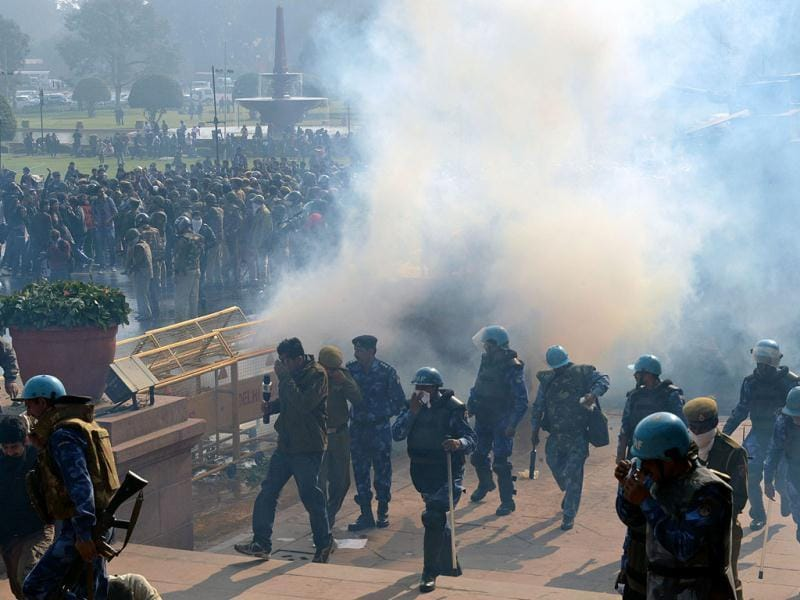 Journalists, police and Rapid Action Force personnel react to a teargas shell that landed in their vicinity during a protest calling for better safety for women following the rape of a student last week, in front of the Government Secretariat and Presidential Palace in New Delhi. AFP photo