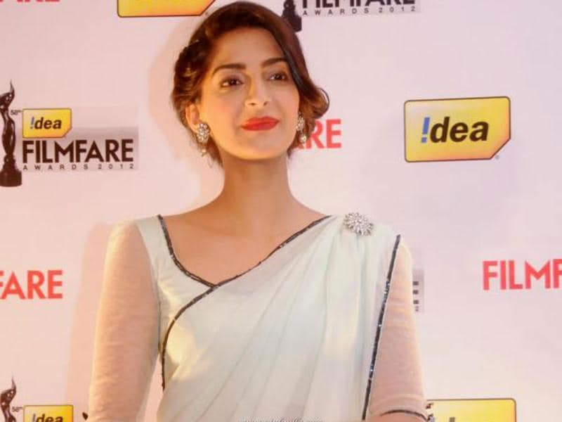 Sonam looked stylish and elegant in a simple white sheen sari with classy earrings and a matching brooch to go with it.