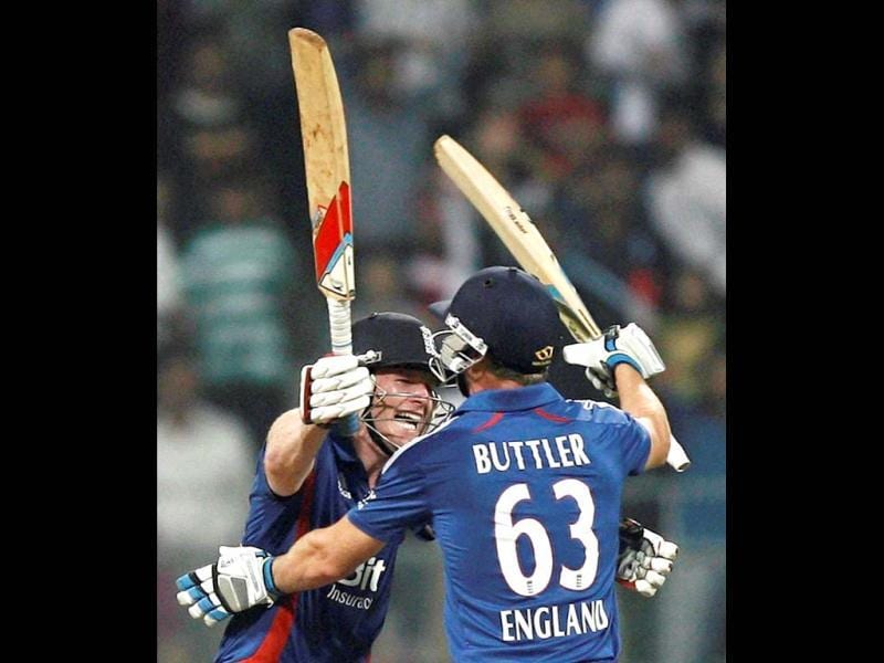 England batsmen Eoin Morgan and Jos Buttler celebrate their victory in the second India-England T20 match in Mumbai. PTI/Shashank Parade