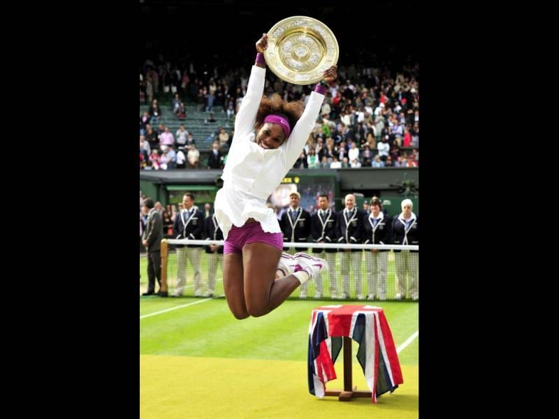 US player Serena Williams celebrates with the trophy, the Venus Rosewater Dish after her women's singles final victory over Poland's Agnieszka Radwanska on day 12 of the 2012 Wimbledon Championships tennis tournament at the All England Tennis Club in Wimbledon, southwest London, on July 7, 2012. Serena Williams won the match 6-1, 5-7, 6-2. AFP Photo