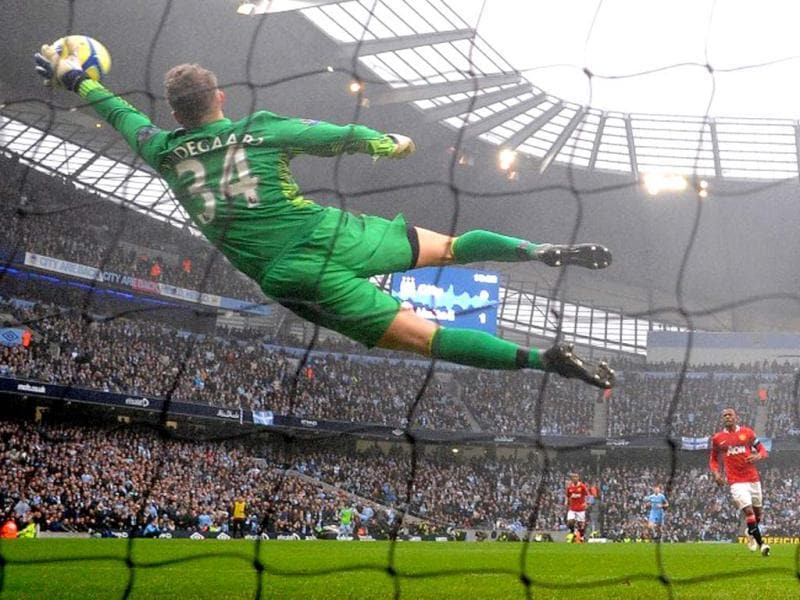 Manchester United's Danish goalkeeper Anders Lindegaard (L) saves a shot from Manchester City's Argentinian forward Sergio Aguero during the FA Cup third round football match between Manchester City and Manchester United at The Etihad stadium in Manchester, north-west England on January 8, 2012. AFP Photo