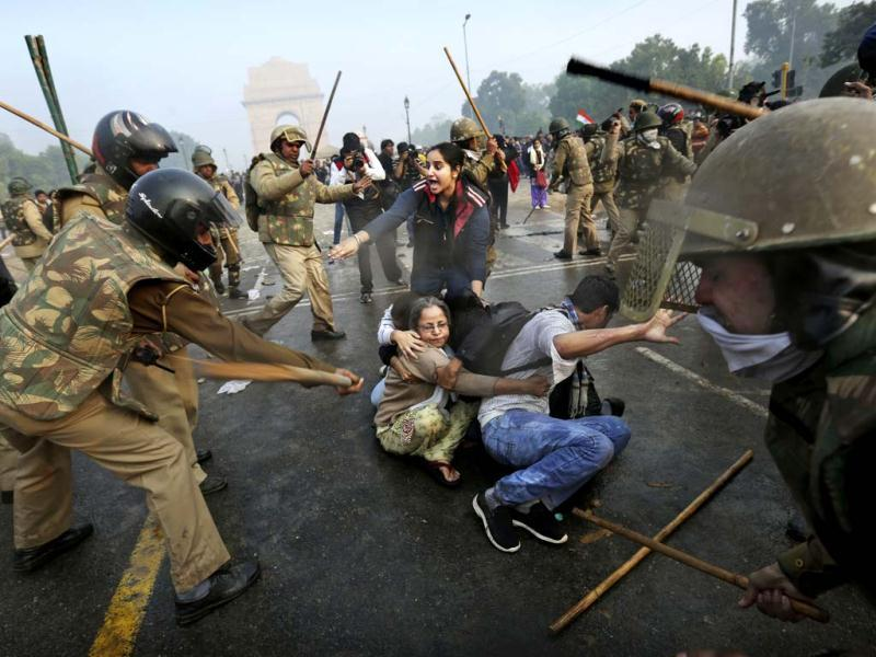 Protesters shield themselves as police beat them with sticks during a violent demonstration near India Gate against a gangrape of a student on a bus last week. AP Photo
