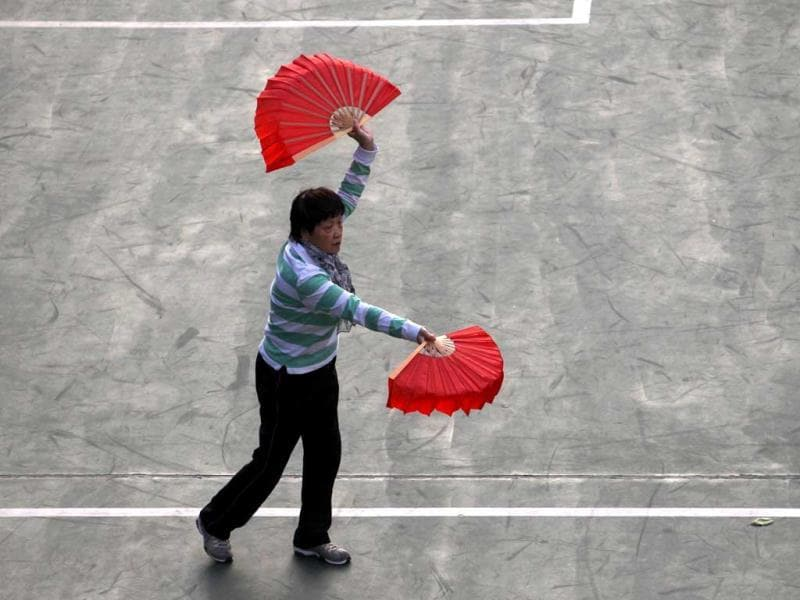 A woman performs tai chi with fans in Hong Kong. Different forms of tai chi excercise untilize the fan, with some being performed slowly and softly, but some include vigorous and fast movements ending with a loud snap of the closing and opening of the fan. AFP Photo
