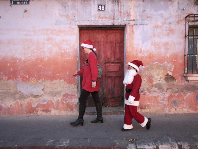Alexander, dressed as Santa Claus, walks beside his mother in Antigua, about 42 km (26 miles) of Guatemala City. Reuters Photo