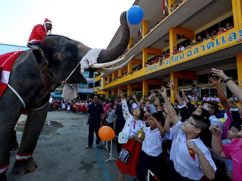 An elephant dressed in a Santa Claus costume gives gifts to students ahead of the Christmas festival at a school in Ayutthaya province. The event was held as part of a campaign to promote Christmas in Thailand. AFP Photo