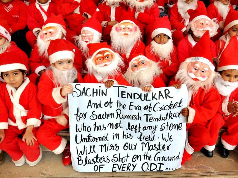 Students dressed as Santa Claus hold a placard paying respect to cricketer Sachin Tendulkar, who announced his retirement, as they celebrate Christmas at a school in Moradabad. (PTI Photo)