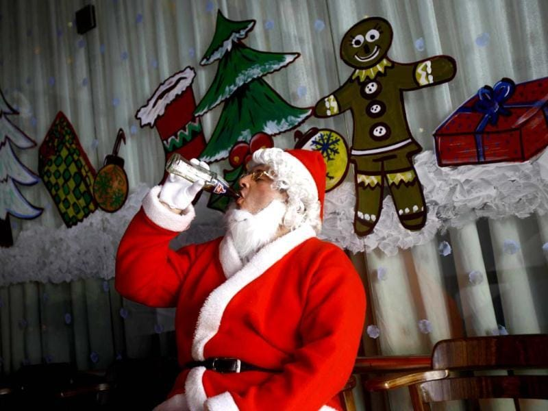 A man dressed as Santa drinks cola as he waits to take part in a Christmas celebration in Mumbai. Although Christians comprise only 2% of the population, Christmas is a national holiday in the country. (AP Photo)