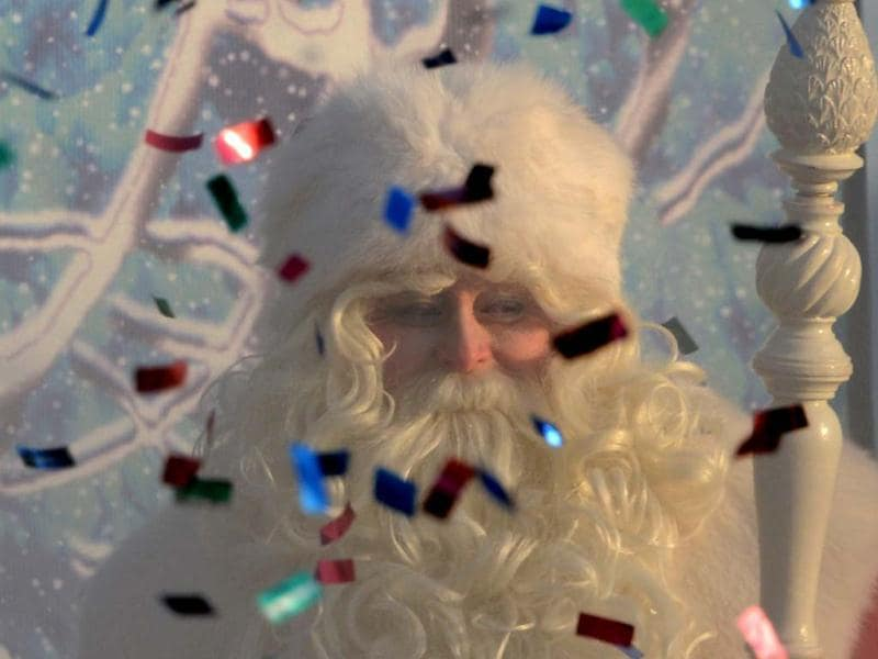An actor dressed as Ded Moroz (Grandfather Frost), the Russian Santa Claus, smiles through smoke from a fire cracker and flying confetti during a welcome ceremony for him in Moscow's Gorky Park. (AFP Photo)