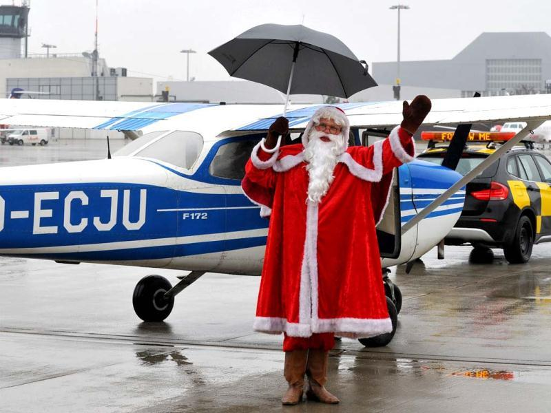 A man dressed as Santa Claus uses an umbrella after arriving with his Christmas Air flight from Lapland at the airport in Dresden, eastern Germany. (AFP Photo)
