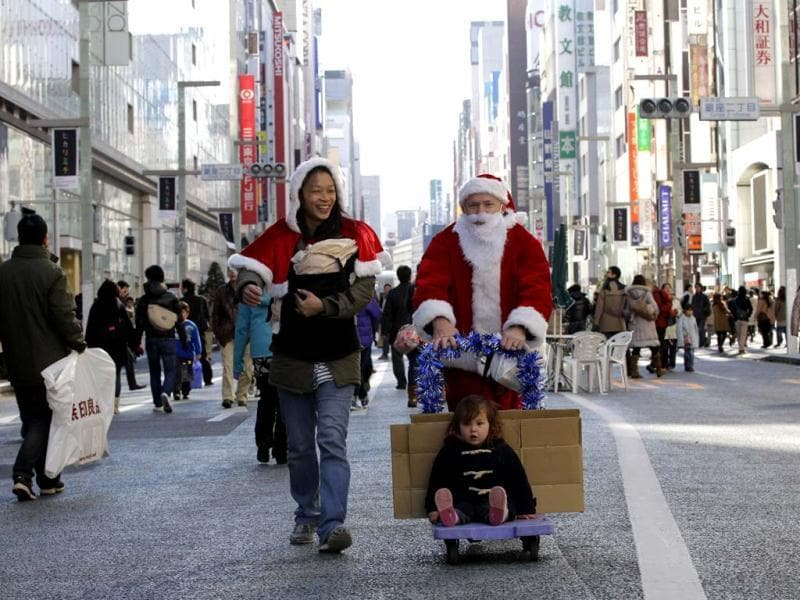 Second Harvest Japan executive director Charles McJilton dressed as Santa Claus, accompanied by his wife and son pushes a cart after handing out picture books attached with donation envelops to passersby on the main street of Tokyo's Ginza shopping district. Second Harvest is one of the largest non-profit food banks based in the United States for the needy people. (AP Photo)