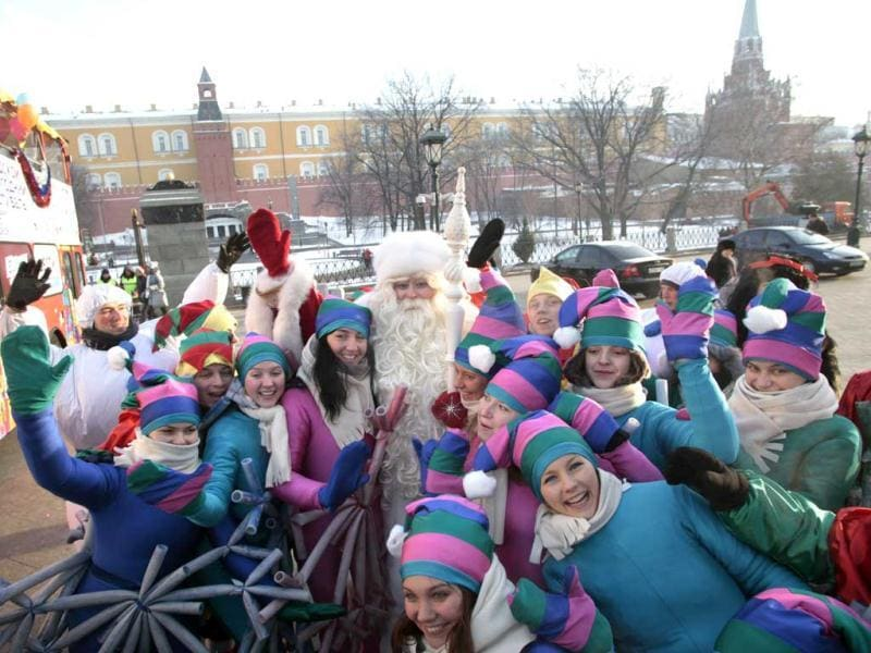 A man dressed up as a Ded Moroz, or Father Frost, the Russian version of Santa Claus, poses with women dressed as Father Frost's assistants at Moscow's Manezh Square. (AP Photo)