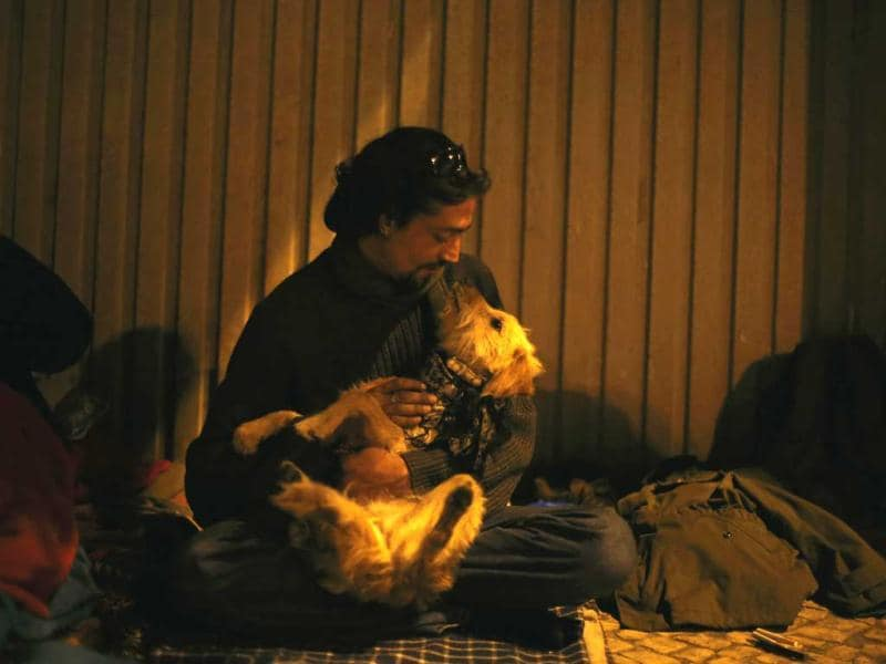 Jorge, 33, who has been living on the streets for three months, plays with his dog as he speaks with a member of the