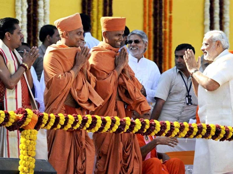 Gujarat chief minister Narendra Modi seeks blessings from Mahants of Swami Narayan Trust during his oath-taking ceremony at Sardar Patel Stadium in Ahmedabad. Cheered by hundreds of thousands, Modi took oath as Gujarat's CM for the fourth time, after leading the BJP to a sweeping win in assembly elections. (PTI Photo)