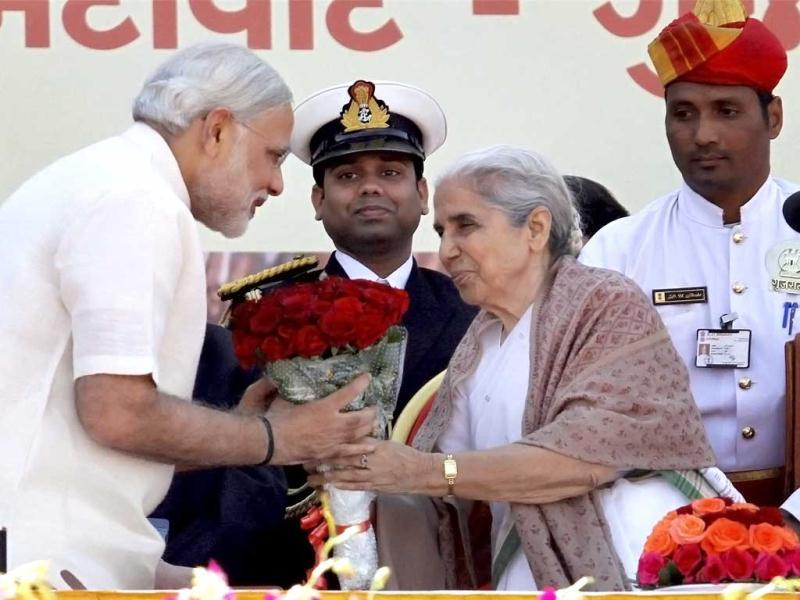 Gujarat Governor Kamla Beniwal greets BJP leader Narendra Modi after he took oath as the Chief Minister of the state for the fourth time at Sardar Patel Stadium in Ahmedabad. An estimated 2.5 lakh people packing the ground roared in joy as a visibly confident Modi took the oath in Gujarati. (PTI Photo)