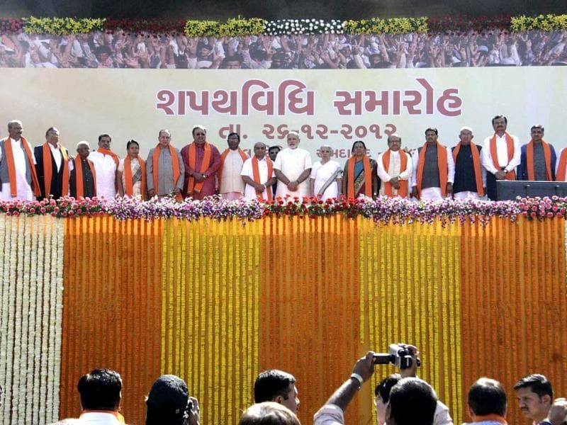Gujarat Chief Minister Narendra Modi with newly sworn- in council of ministers at Sardar Patel stadium in Ahmedabad. Modi was sworn in along with seven ministers of Cabinet rank and nine Ministers of State. (UNI Photo)