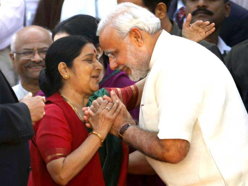 Gujarat Chief Minister Narendra Modi exchanges greetings with senior BJP leader Sushma Swaraj during his oath-taking ceremony at Sardar Patel Stadium in Ahmedabad. A galaxy of top BJP leaders and those of its allies were present during the swearing-in ceremony. (PTI Photo)