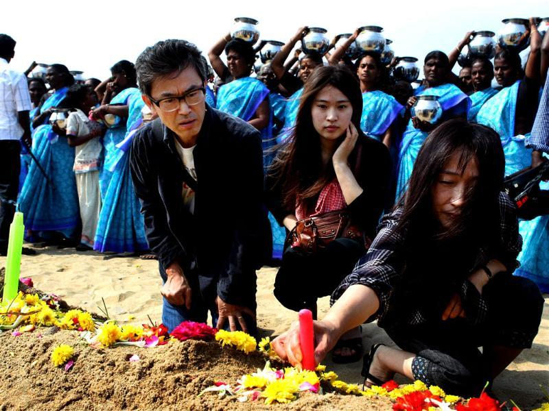 Foreign tourists offer prayers for the victims of the 2004 tsunami at Marina Beach in Chennai. PTI/R Senthil Kumar