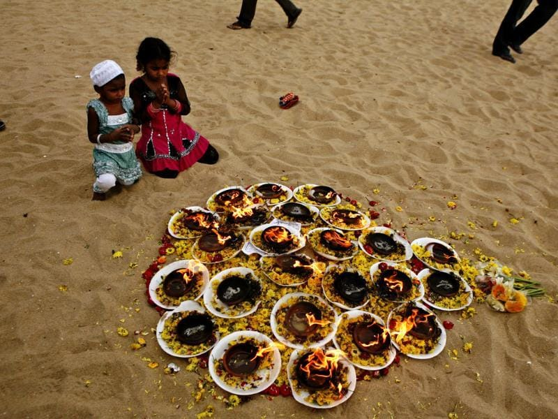 Kids offer prayers at Marina beach, that was hit by tsunami in 2004, in Chennai. The December 26, 2004 tsunami killed around 230,000 people in 12 Indian Ocean nations, from Thailand to Sri Lanka. AP/Arun Sankar K