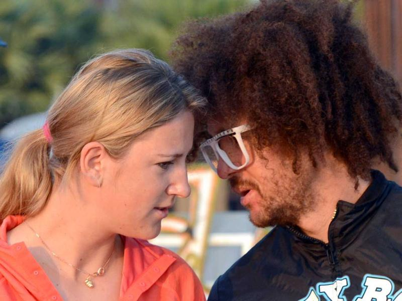 World number one woman's tennis player Victoria Azarenka of Belarus (L) and her boyfriend, US rapper Redfoo (R), chat as they meet with Buddhist monks at a hotel in Thailand's resort seaside town of Hua Hin. (AFP Photo)