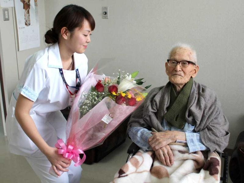 This picture shows Jiroemon Kimura, world's oldest man, receiving a flower bouquet from a nurse at a hospital in Kyotango, western Japan. (AFP file photo)
