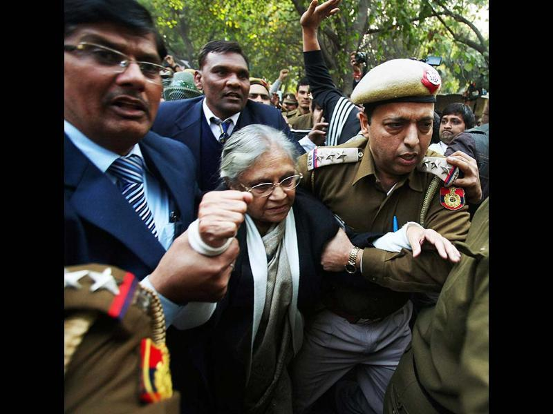 Security personnel escort Delhi chief minister Sheila Dikshit after anti-rape protesters stopped her at Jantar Mantar from taking part in a demonstration to mourn the death of the gangrape victim in New Delhi. PTI/Manvender Vashist