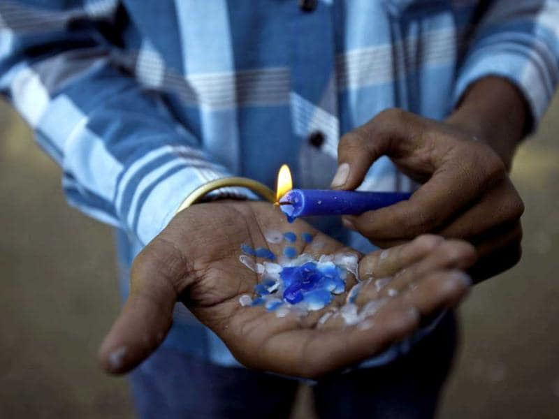 A protester holds a candle as he attends a gathering to mourn the death of the gang rape victim in Mumbai. AP Photo