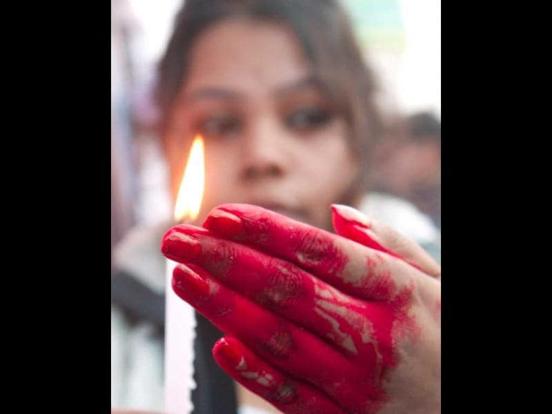 Youth Congress worker holding a lighted candle at a protest rally at Dorina Crossing in Kolkata. Subhendu Ghosh/HT