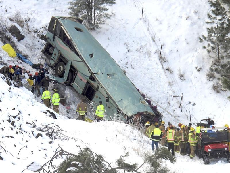 Emergency personnel respond to the scene of a multiple-fatality accident after a tour bus careened through a guardrail along an icy highway and fell several hundred feet down a steep embankment about 15 miles east of Pendleton, Ore. AP/East Oregonian, Tim Trainor