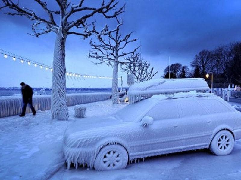 A man walks past an ice covered car on the frozen waterside promenade at Lake Geneva in the city Versoix, near Geneva in early February. AFP/Fabrice Coffrini