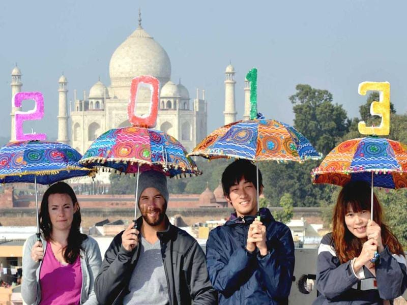 Tourists hold up umbrellas to welcome 2013 at a hotel terrace near the historic Taj Mahal in Agra on Monday. (UNI Photo)
