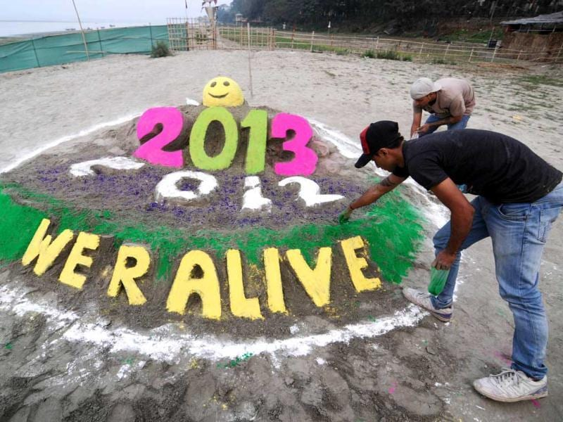 Youths make an installation to welcome the new year 2013 at the banks of the Brahmaputra river in Guwahati. (AFP Photo)