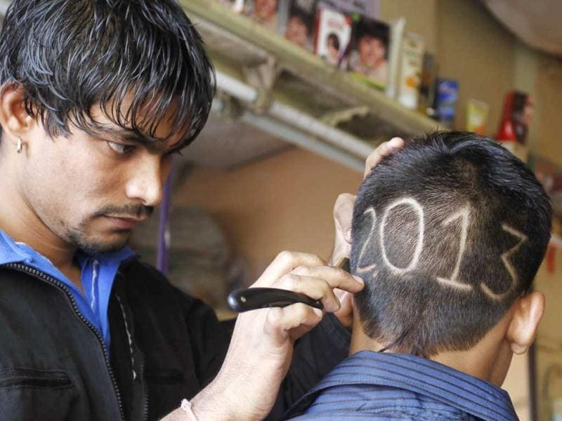 A barber gives finishing touches to the hair style of a young boy with numbers to welcome the New Year 2013 in Ahmedabad. (AP Photo)
