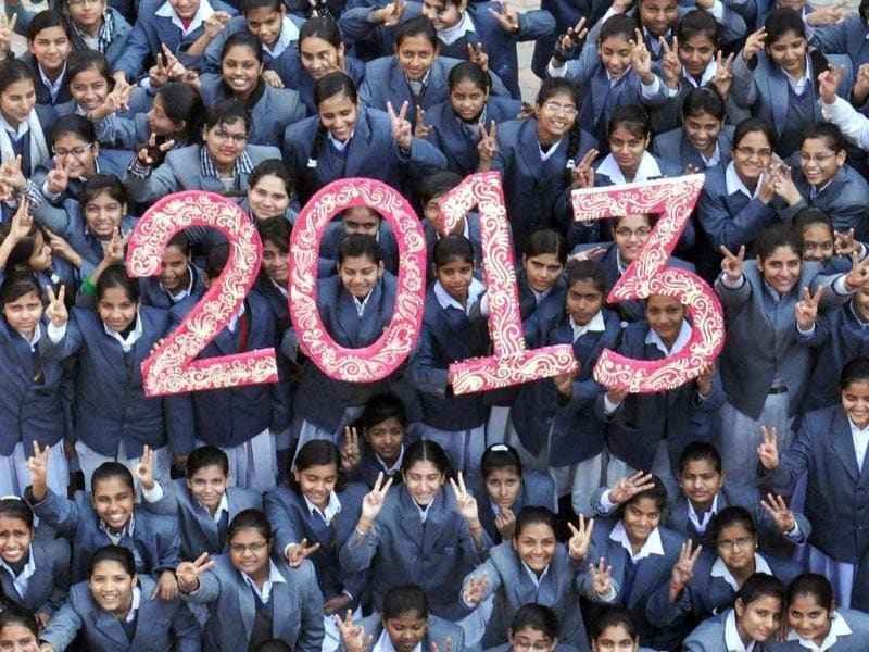 Girls welcome the New Year 2013 at their school in Mathura. Sydney will kick off a wave of dazzling firework displays welcoming in 2013. (PTI Photo)