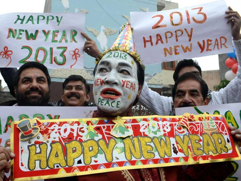 Indian revellers hold placards in Amritsar as they prepare to welcome new year 2013. (AFP Photo)