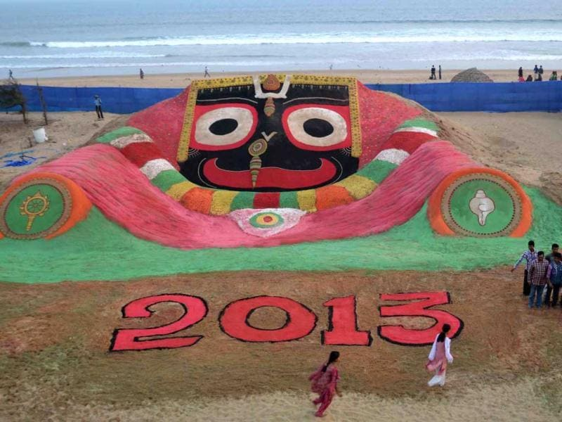 People look at the sand sculpture for the new year 2013 created by sand artist Sudarshan Pattnaik at the Puri sea beach. (AP Photo)