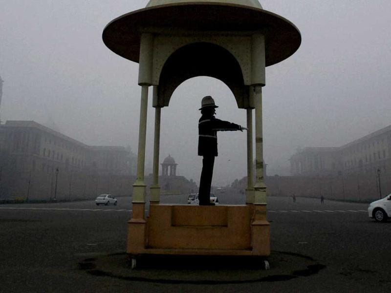 A traffic policeman discharges his duty at Vijay Chowk during a cold and foggy morning in New Delhi on the first day of the New Year. PTI/Atul Yadav