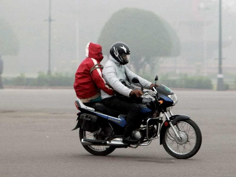 A couple riding a motorcycle during a cold and foggy morning in New Delhi on the first day of the New Year. PTI/Atul Yadav