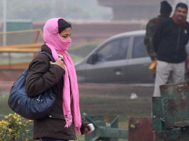 A girl takes protection against the biting cold as she walks along a road in New Delhi on New Year day. PTI/Kamal Singh