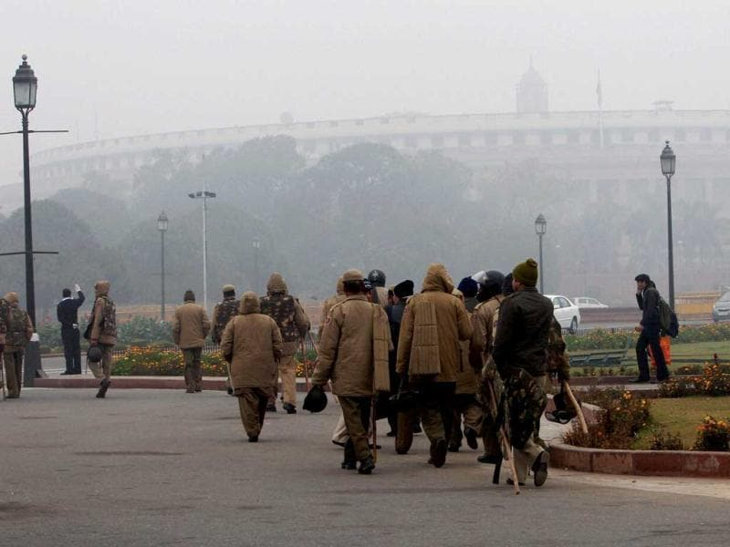Security personnel moving along a road near parliament during a cold and foggy morning in New Delhi on the first day of the New Year. PTI/Kamal Singh