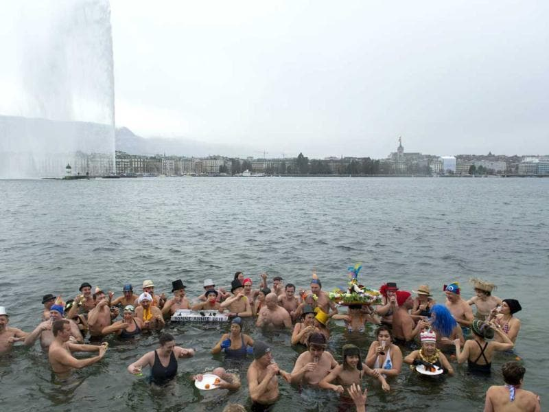 People carry glasses of champagne while swimming in the chilly water during the annual swim in Lake Geneva, on New Year's day. AP Photo