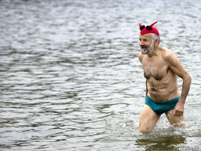 A man with a fancy cap leaves the water after he attended the annual New Year's swimming at Oranke Lake in Berlin. AP Photo