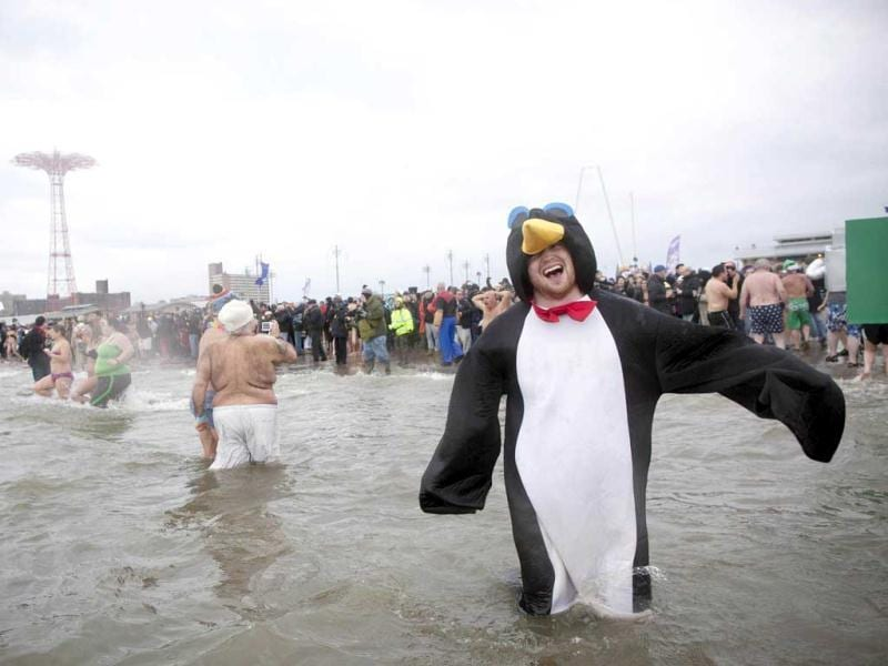 A man dressed as a penguin enters the water while taking part in the Coney Island Polar Bear Club's annual New Year's Day Polar Bear Swim in New York's Coney Island. Reuters Photo