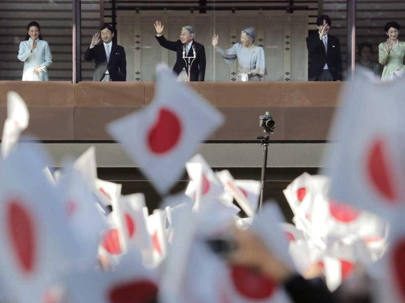 Japan's Emperor Akihito, third left, and Empress Michiko, third right, wave to well-wishers with their family members from a balcony during the new year's public appearance at the Imperial Palace in Tokyo. AP Photo