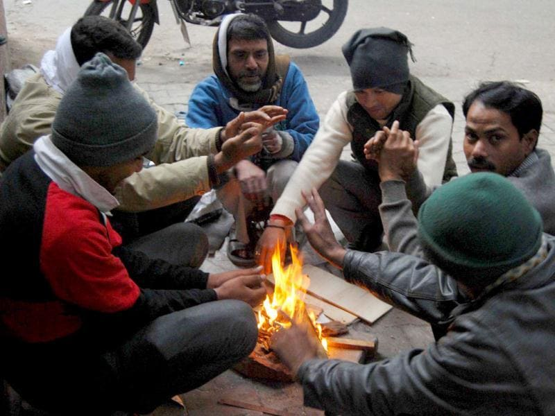 People warm themselves around a small fire on a cold day in New Delhi as maximum temperature dropped to to 9.8 deg Celsius, the lowest in 44 years. UNI